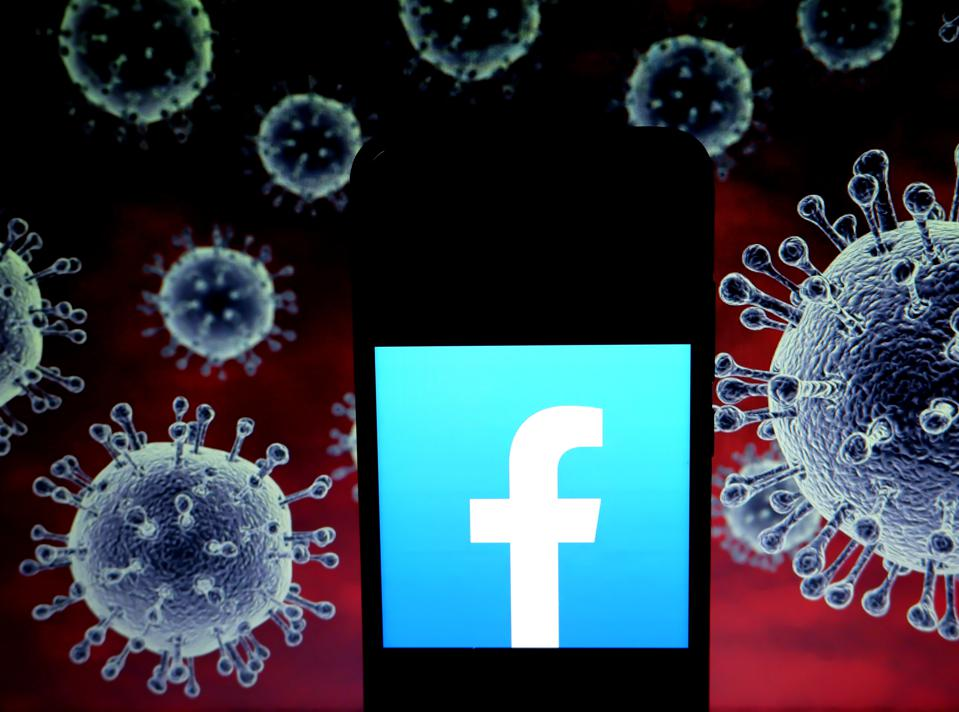 The Facebook logo on a smartphone with highly magnified virus images in the background