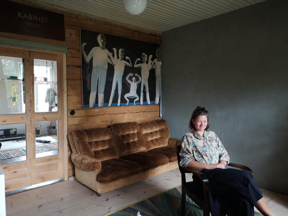 artist in chair with painting and sofa behind her