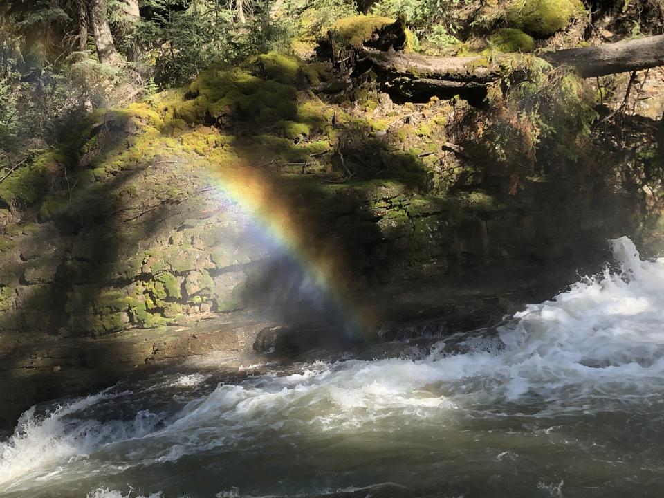 A rainbow forms in the mist over Ousel Falls, Big Sky, Montana.