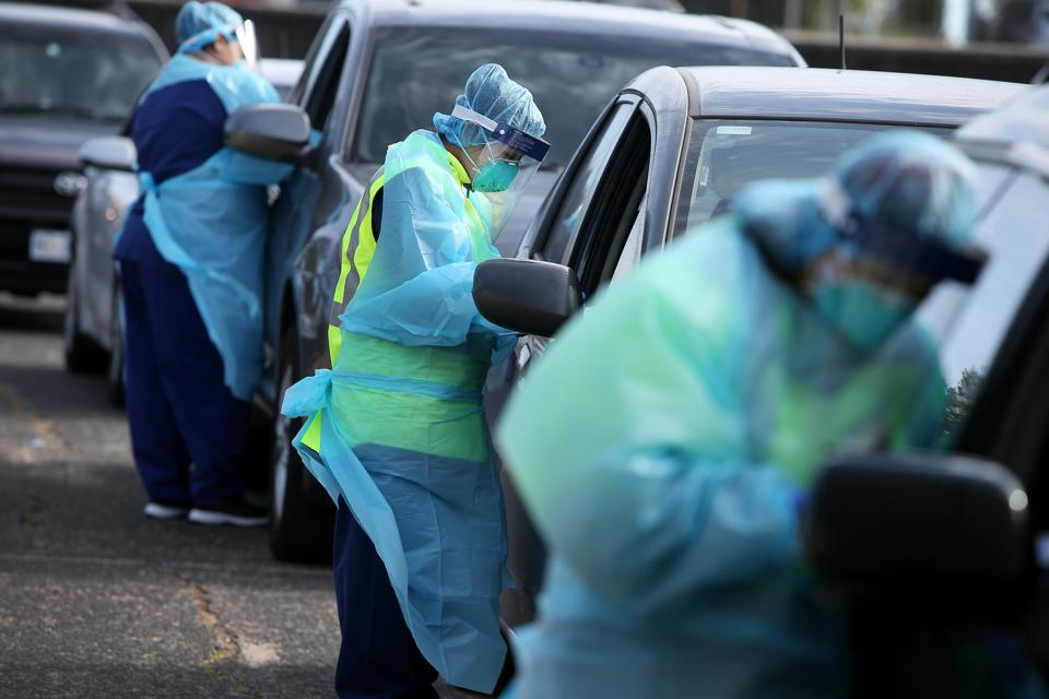 Health staff in PPE administering Covid-19 Testing to people inside their cars