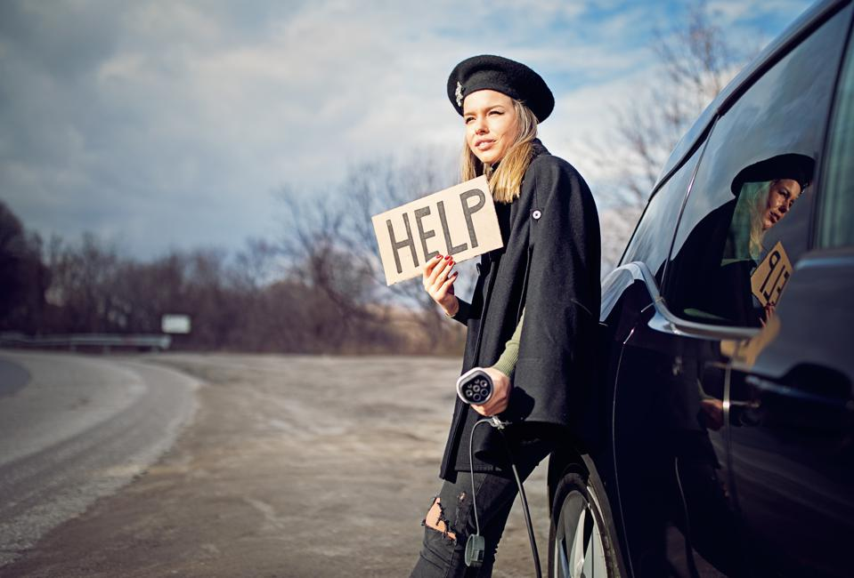 Young girl with electric car without power in the battery is looking for help