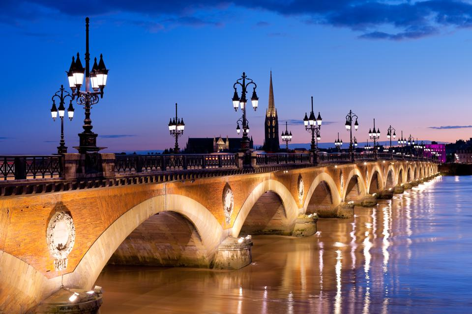 Night view on the Pont de pierre (Stone Bridge in English) bridge in Bordeaux that connects the Left Bank of the Garonne River to the Right Bank