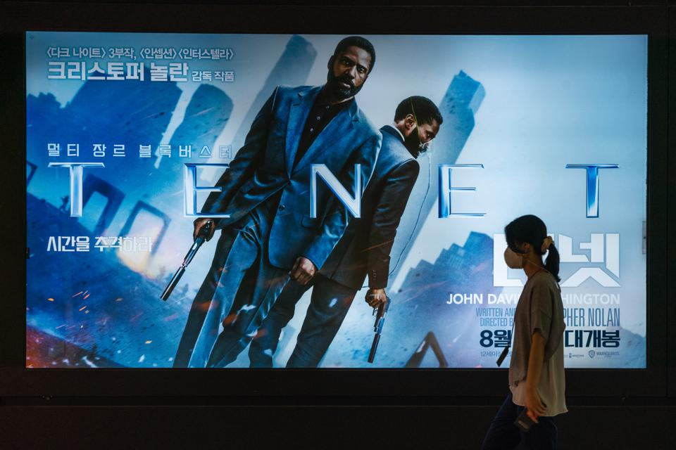A woman wearing a protective mask walks by a billboard of...