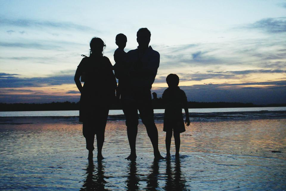 Silhouette Family Standing At Beach Against Sky During Sunset