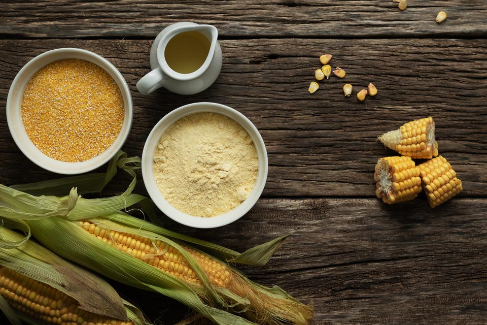 Corn oil, polenta corn grits, corn flour in a porcelain bowl on a wooden table. Ears of corn and slices of corn next to bowls. Gluten free healthy foods.