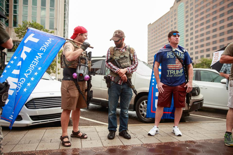 A group of men carry AR-15 style rifles during the We Will...