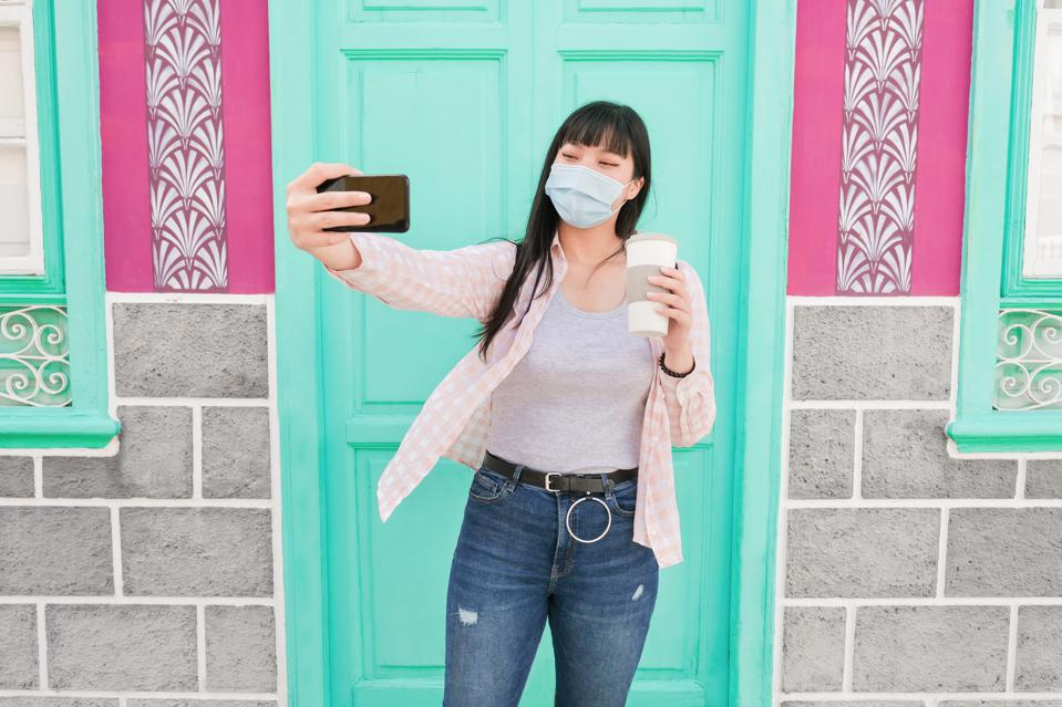 Asian woman wearing a protective face mask in prevention for coronavirus taking a selfie