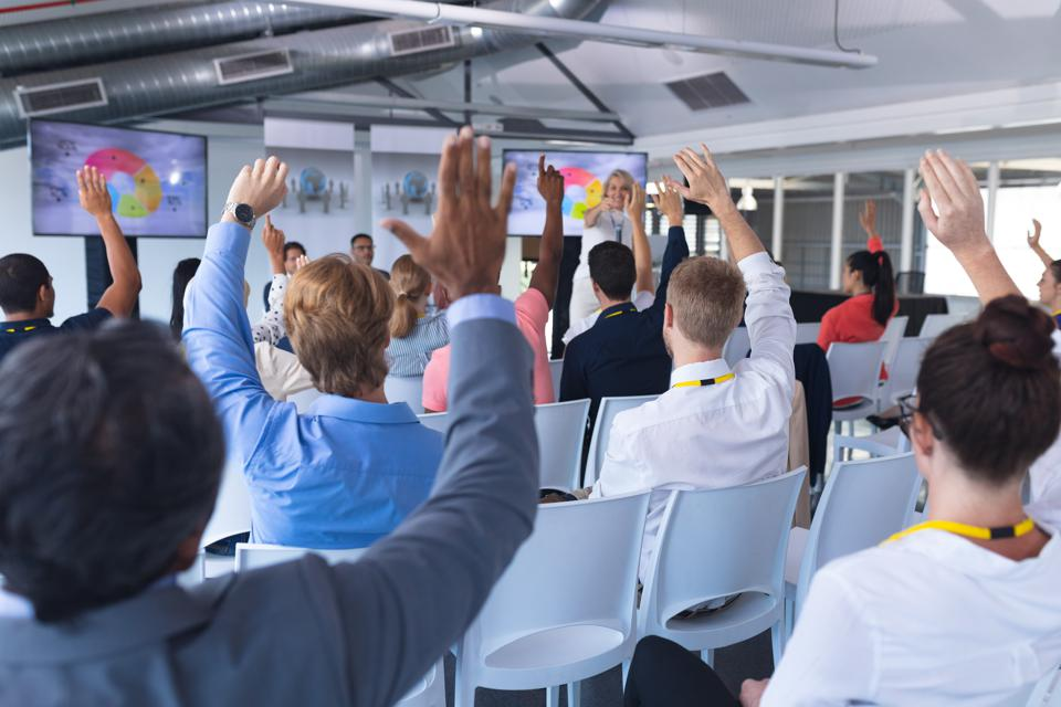 Audience raising their hands in a training session for diversity and inclusion