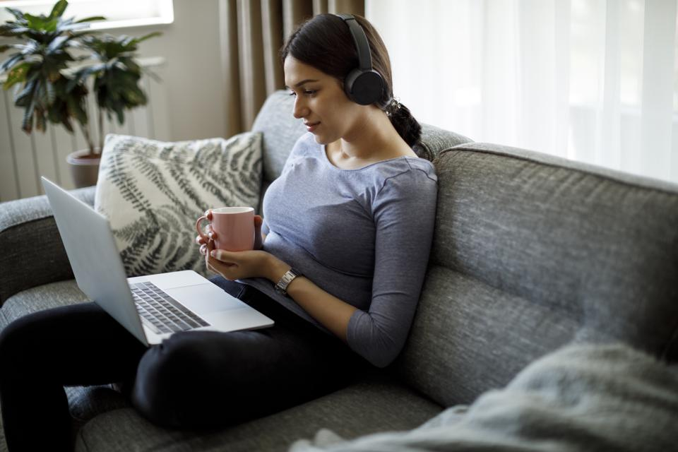 Smiling young woman with headphones using laptop at home