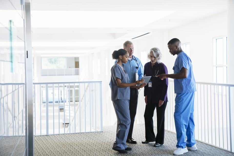 Doctors and nurses discussing digital tablet