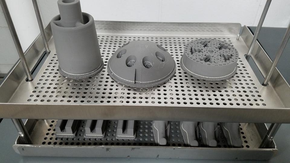 Metal 3-D printed parts await post-processing.