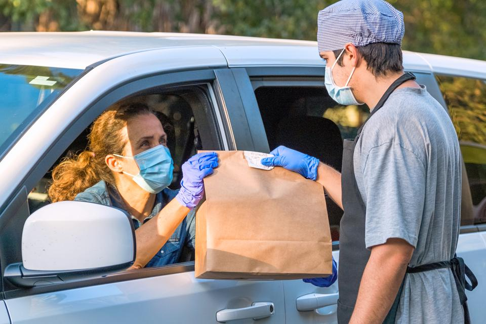 Mature woman picking up her restaurant food from her car at a Curbside pickup