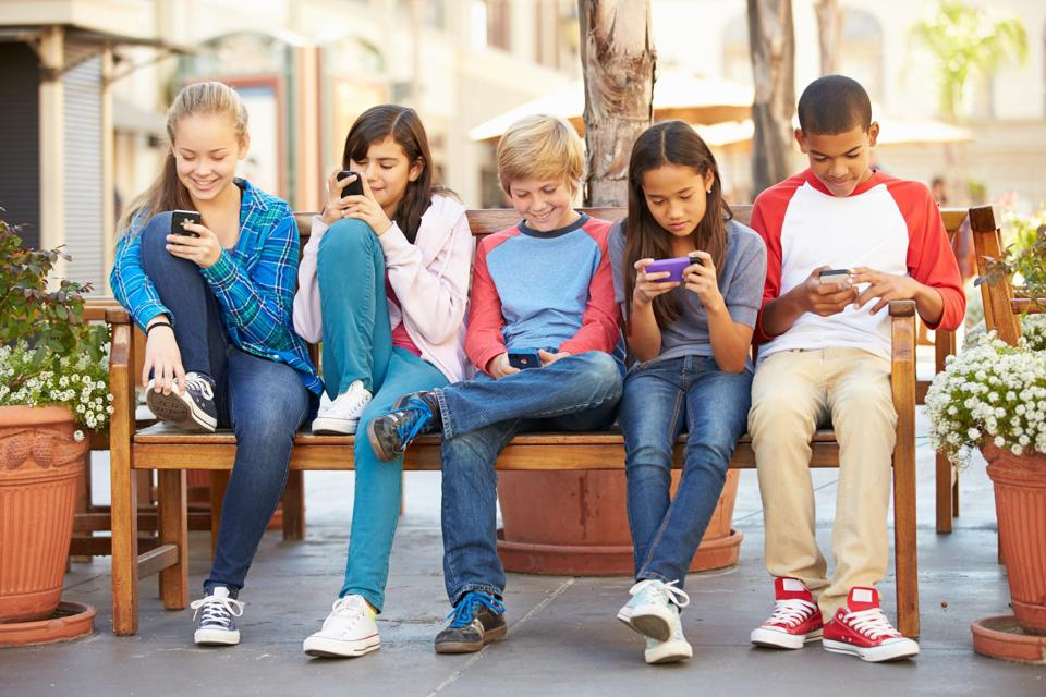 kids sitting on a bench using smartphones