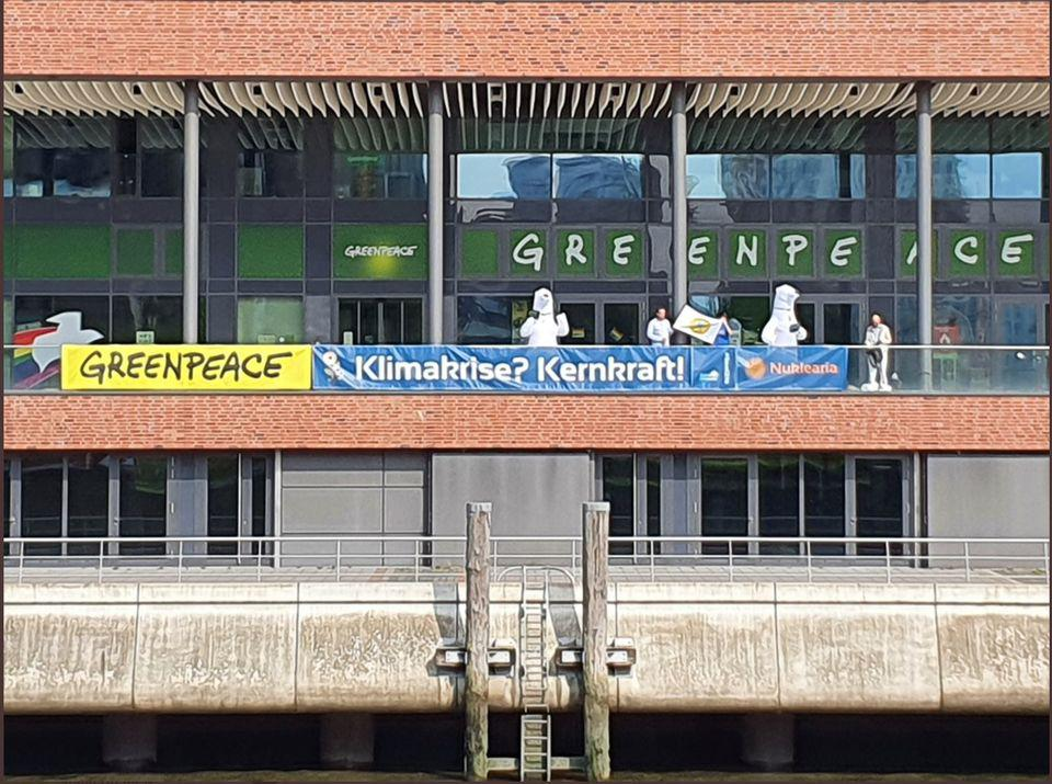 "Pro-nuclear activists drop a banner in front of Greenpeace's Germany headquarters. It reads, ""Climate Crisis? Nuclear energy!"""