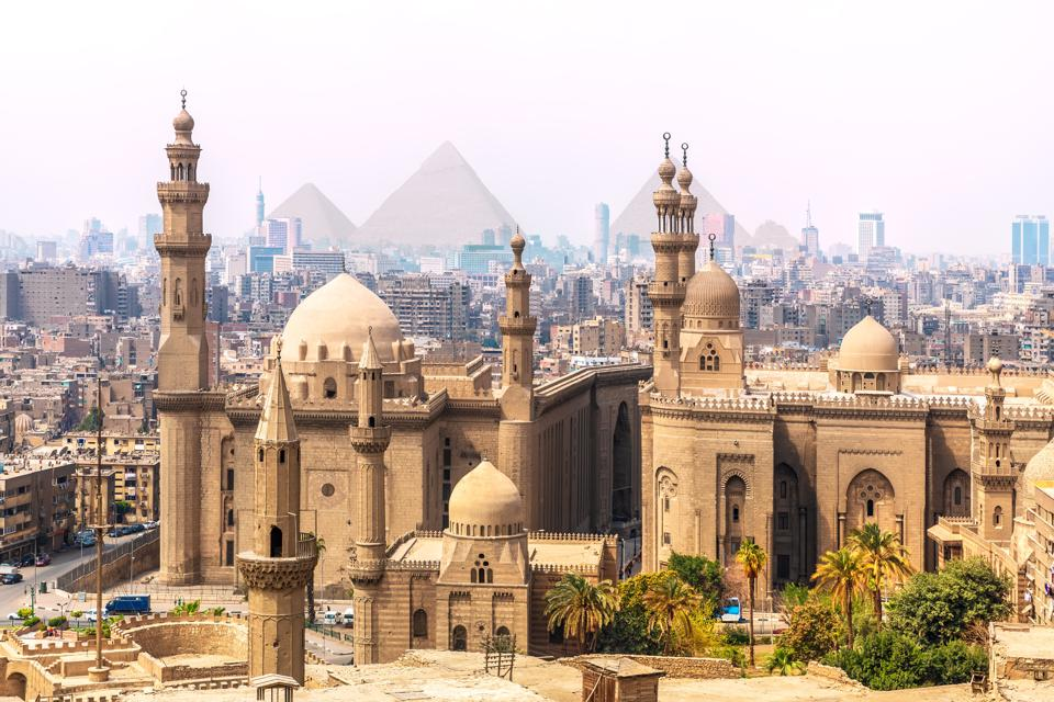 The Mosque of Sultan Hassan and the Pyramids in the background, Cairo, Egypt covid-19