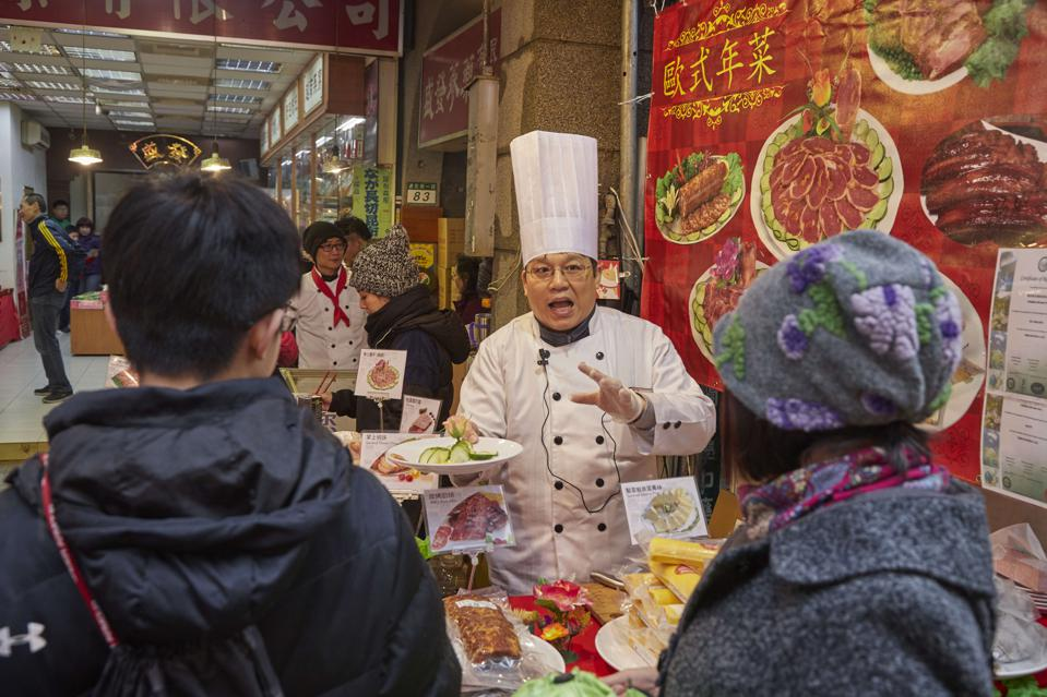 A chef talks to customers and offers samples to try at the...
