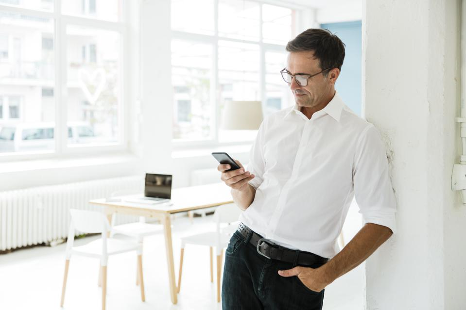 Businessman looking on cell phone in bright office
