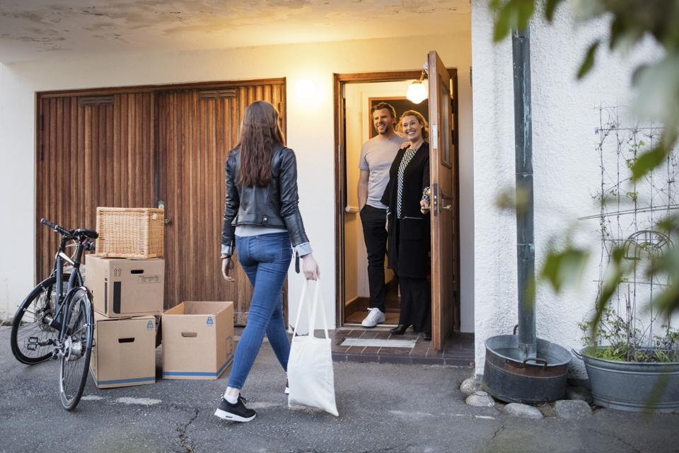 Parents looking at daughter walking by cardboard boxes and bicycle outside house