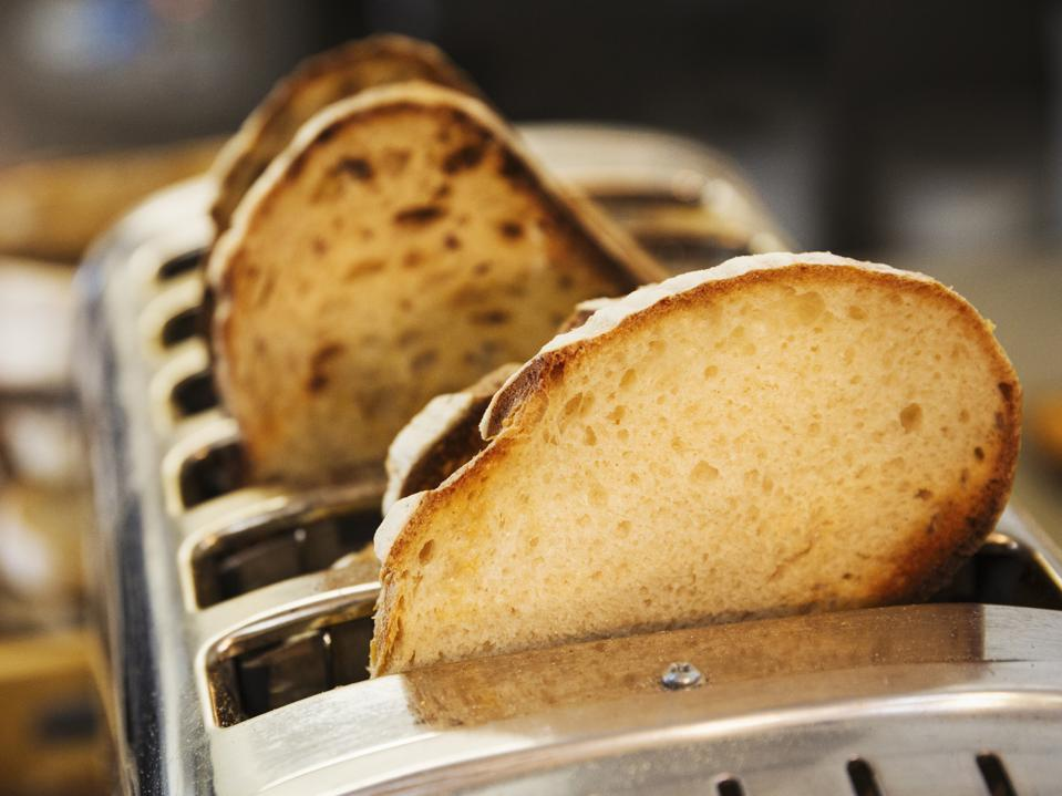 Close up of slices of bread in a stainless steel toaster.