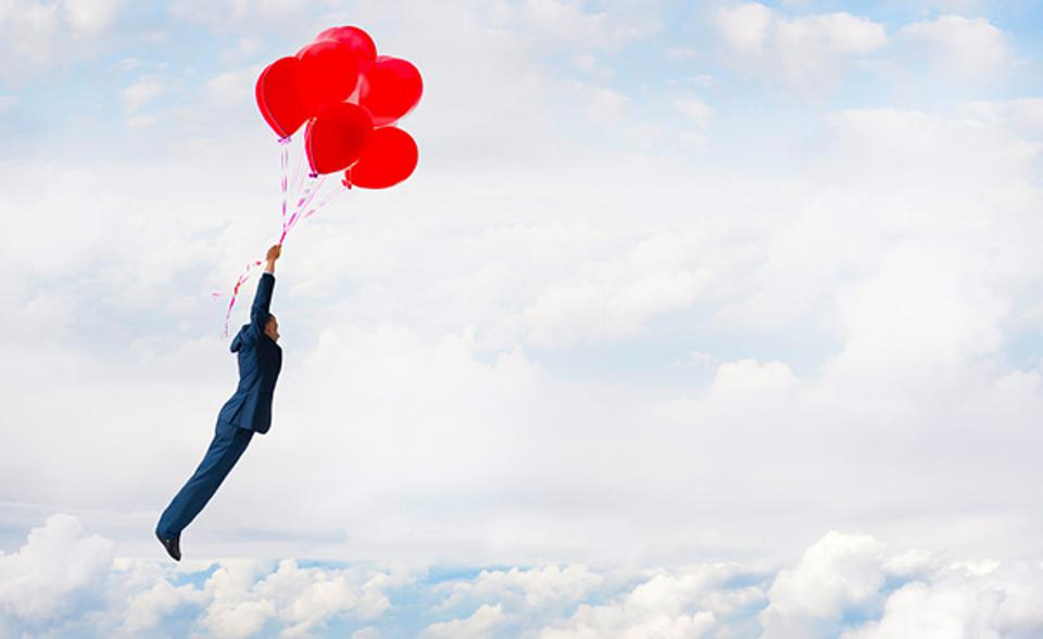 Red balloons man holding on in air