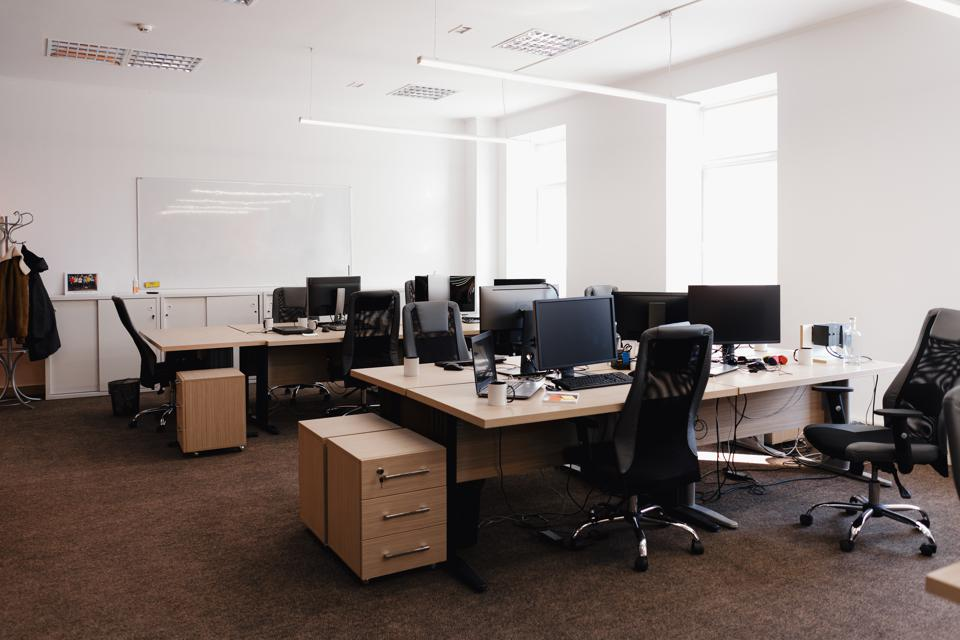 Empty office space with desks, monitors and chairs, brown carpet with dingy tone