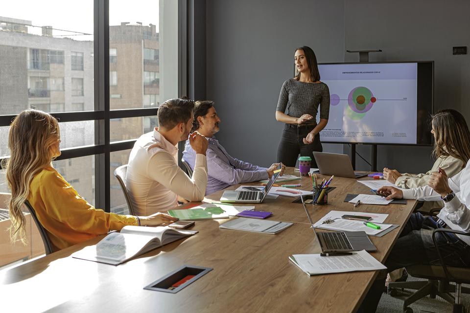 A Young Millennial Generation Latin Lady Dressed In Casual Clothes, Makes A Presentation To Her Coworkers On Business Performace Using A Large Flat Screen Monitor In The Office Conference Room.