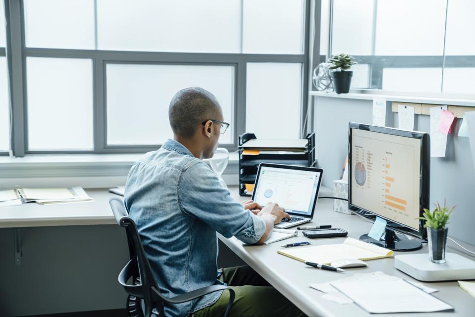 internet marketing Black businessman using laptop in office