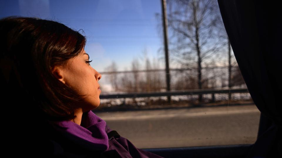 Young woman travelling by bus, looking sad or thoughtful