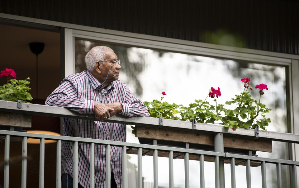91 year old man standing on his balcony, looking away