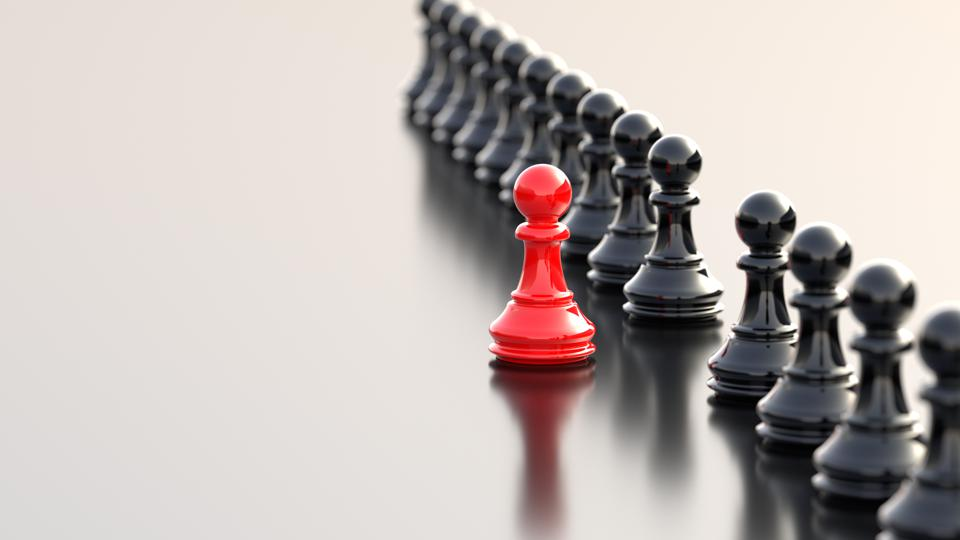 Chess with red pawn standing out among black pawns
