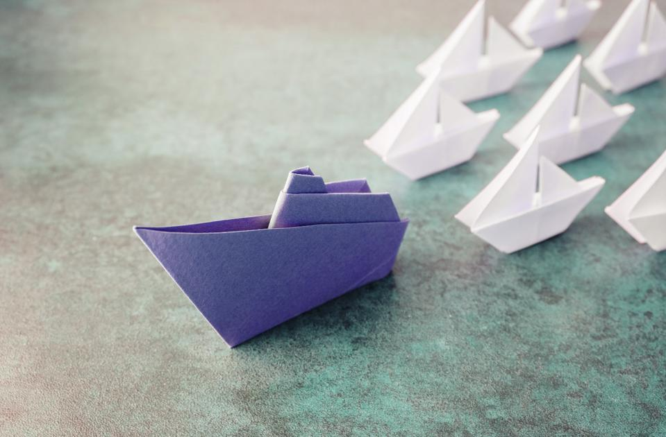 purple paper boar with smaller white paper boats following it