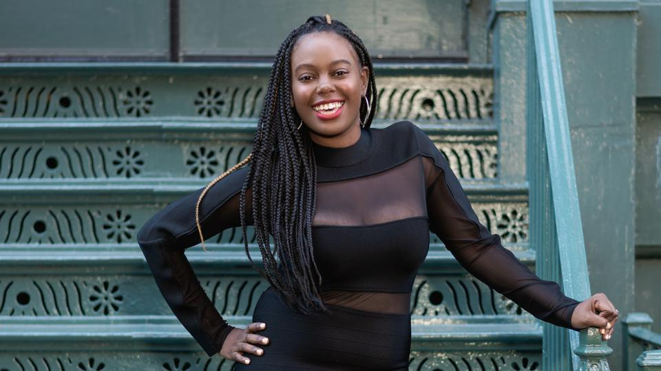 Gabby Cudjoe-Wilkes stands smiling in front of an outdoor staircase
