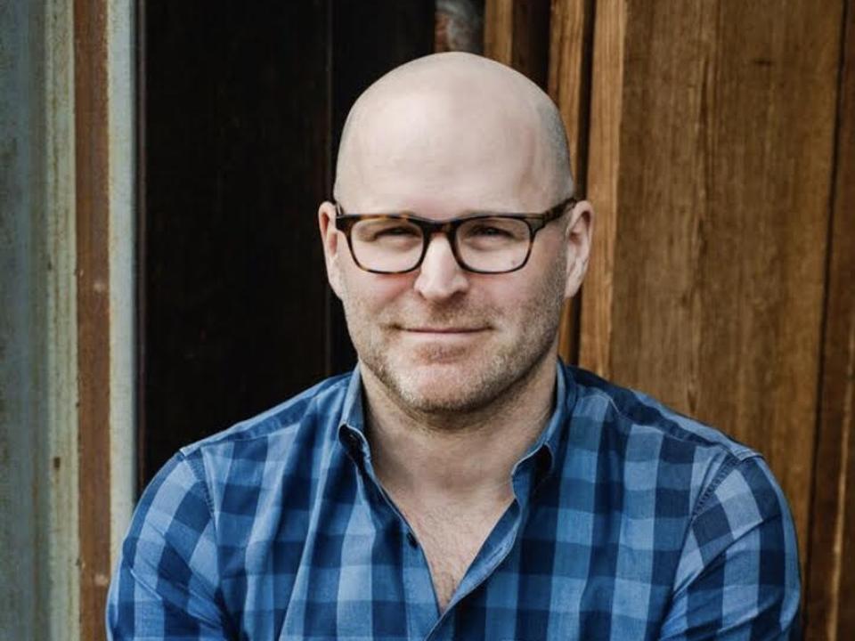 Headshot of Harmann in a checkered blue shirt.
