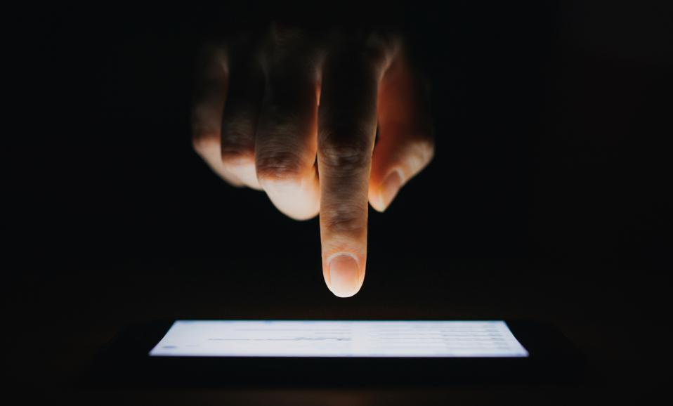 Close up of woman's hand checking emails on smartphone  against black background