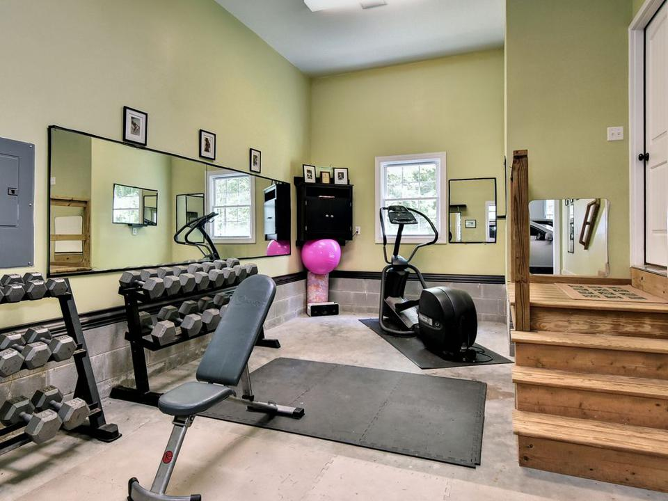 Home gym equipment including barbells and workout mat.