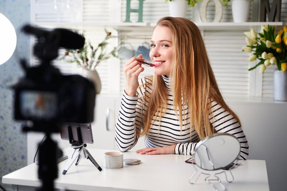 Beauty blogger streaming daily make-up routine tutorial at camera on tripod.