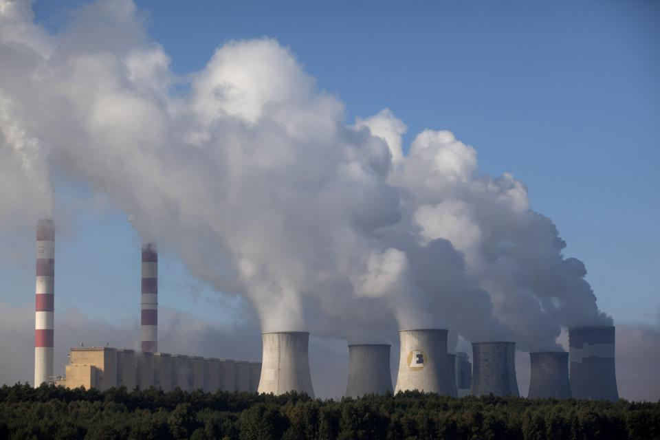 Chimneys at a coal fired power plant in Poland belch smoke and steam into a blue sky.