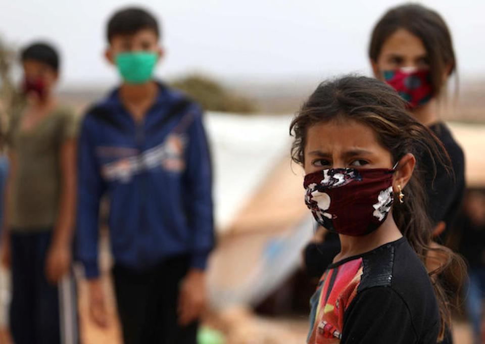 Children wear face masks sewn by displaced Syrian women at a camp for internally displaced persons near the town of Maaret Misrin in Syria's northwestern Idlib province, amidst the crisis of the COVID-19 pandemic.