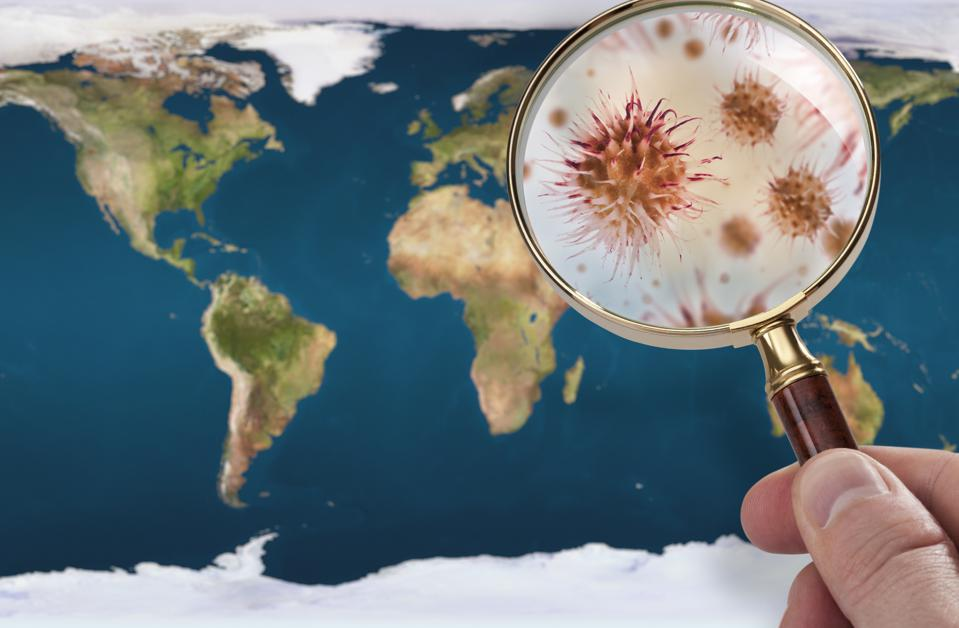 A hand examining the world with a magnifying glass and he sees a magnified virus.
