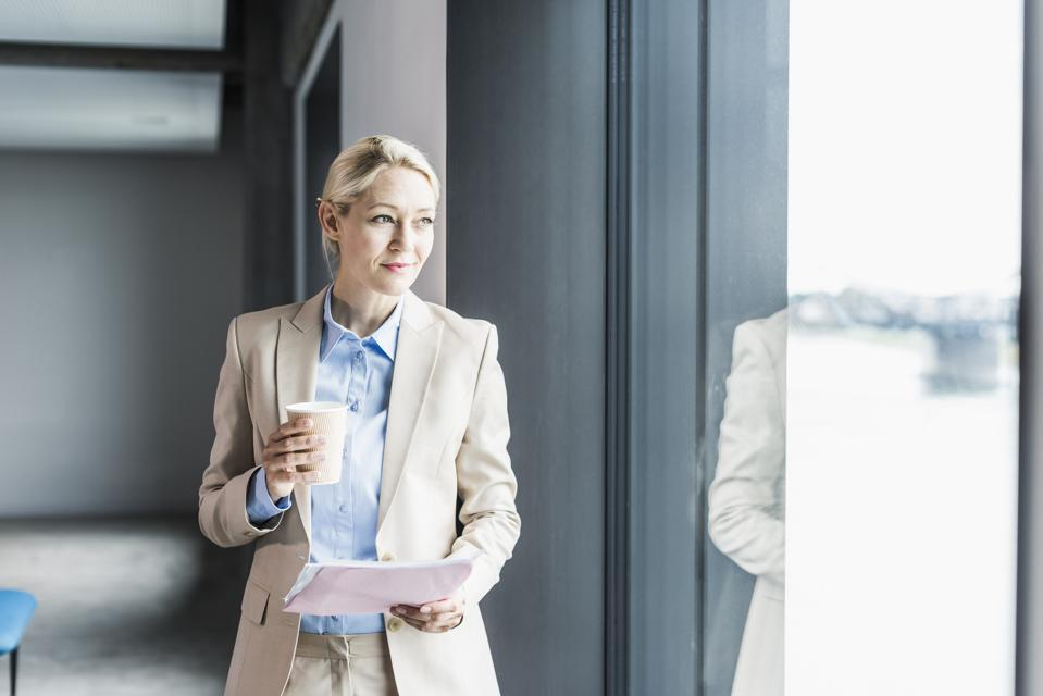 Businesswoman with coffee and documents at the window