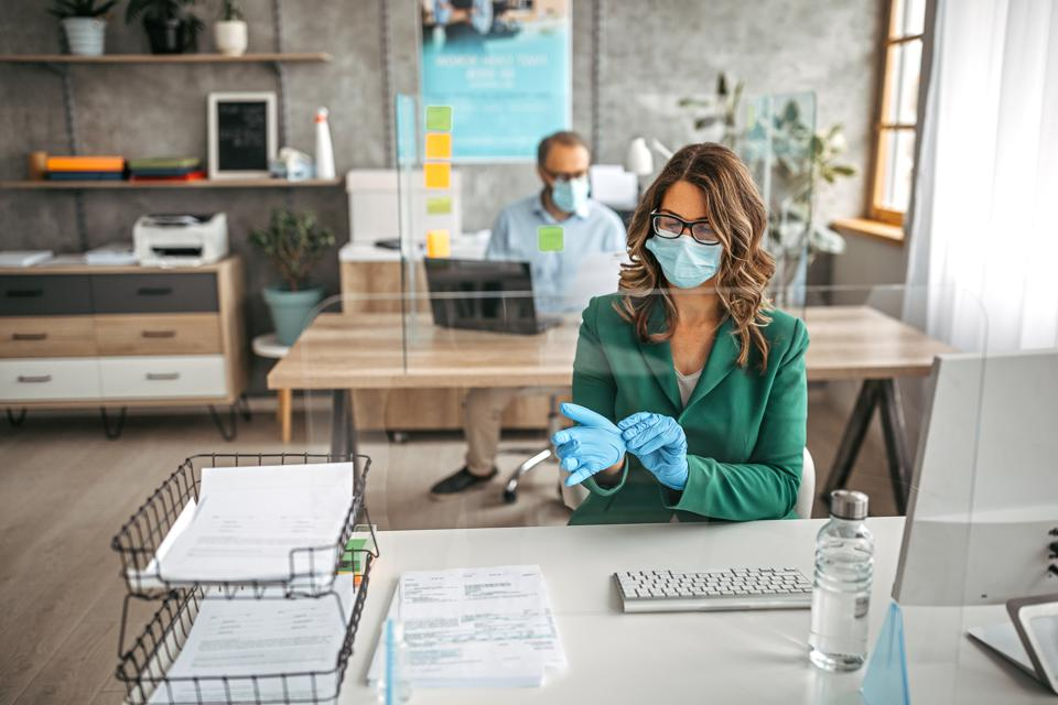Businesswoman putting on protective gloves in the office
