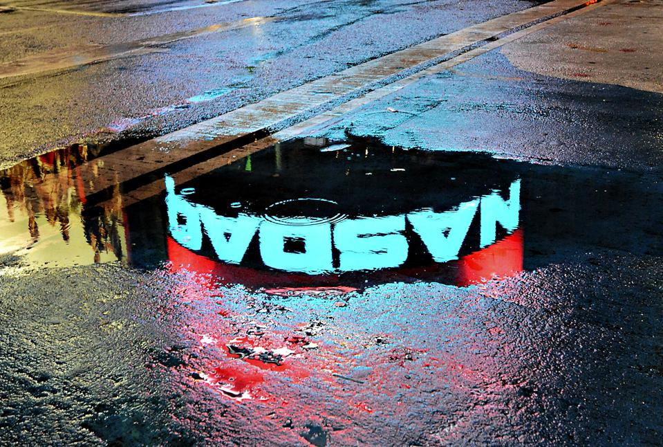 NASDAQ sign is reflected in a puddle