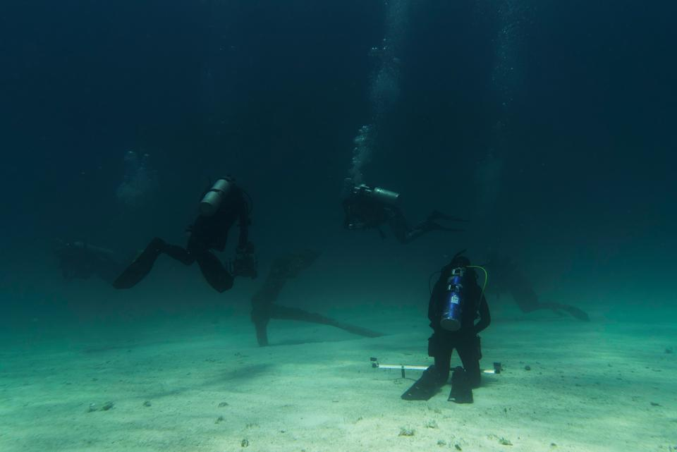 A team of divers surround a huge, rusted anchor in blue waters.