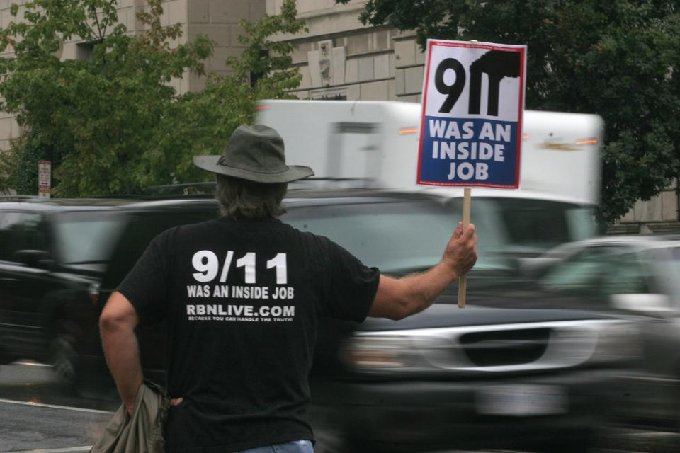 A protestor holds a sign claiming the 11