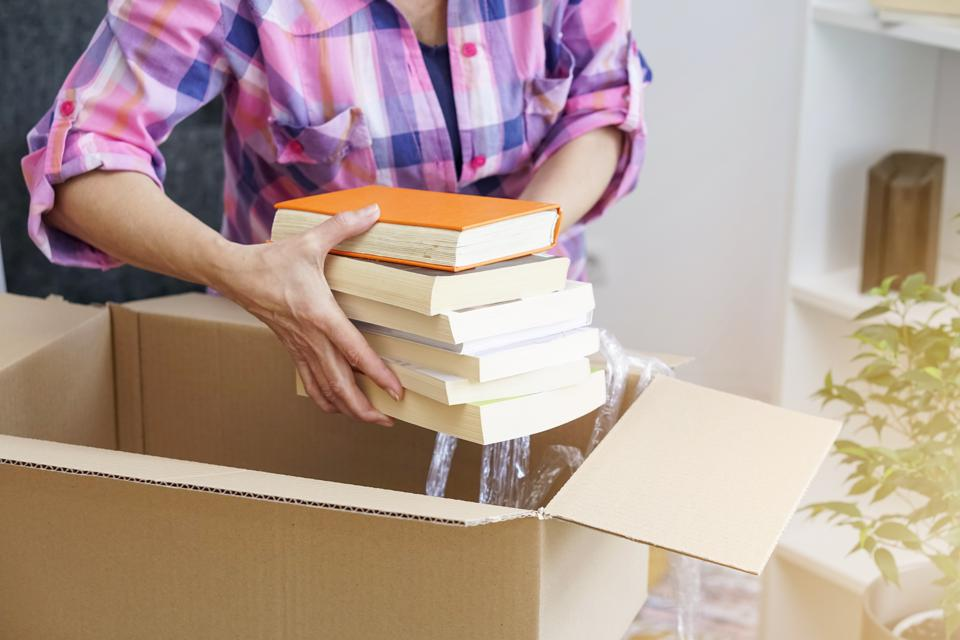 woman putting books into a box