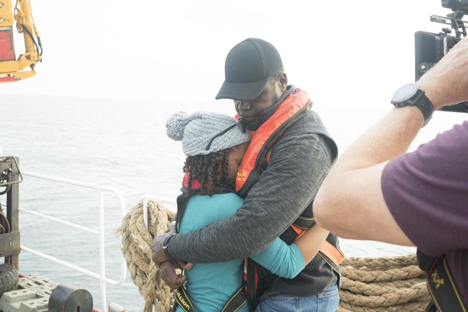 A young woman embraces a middle-aged man on board a ship.
