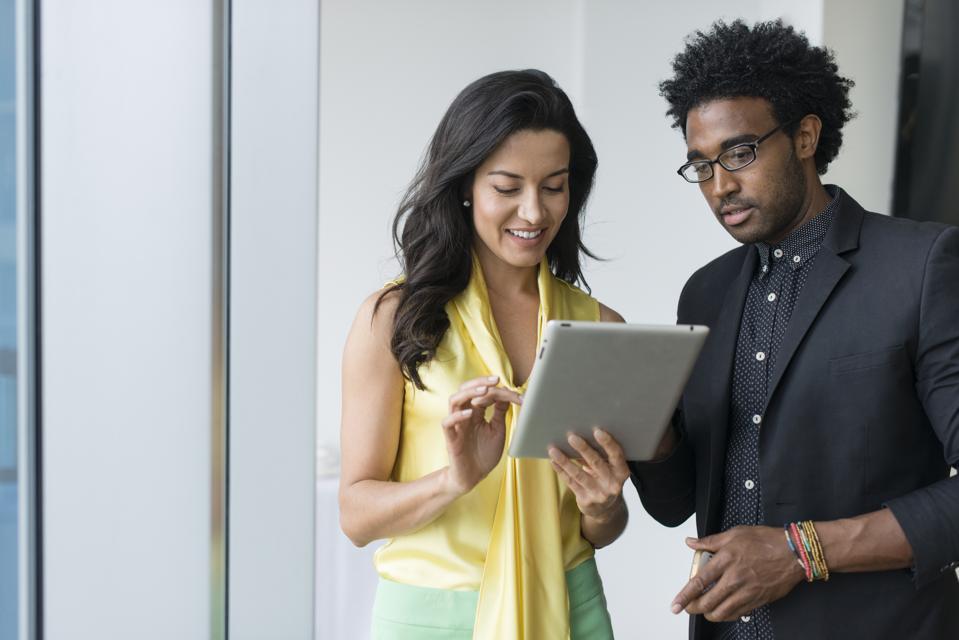Hispanic business people using digital tablet in office