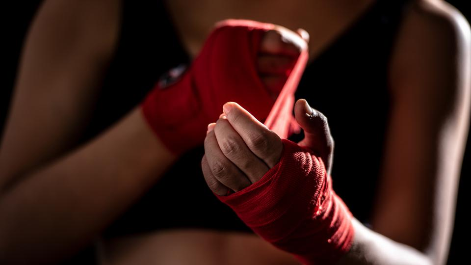 Health care women are exercising by punching and are wrapped in red cloth at the hands before punching in the gym.