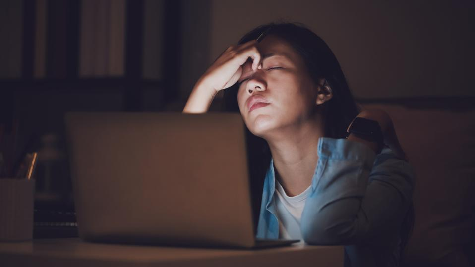 Asian woman student or businesswoman work late at night. Concentrated and feel sleepy at the desk in dark room with laptop or notebook.Concept of people workhard and burnout syndrome.