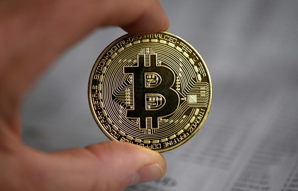 A picture of bitcoin, a digital currency, being held by a human hand.